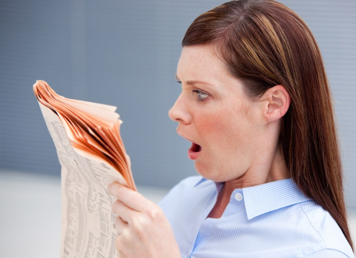 Astonished businesswoman reading newspaper